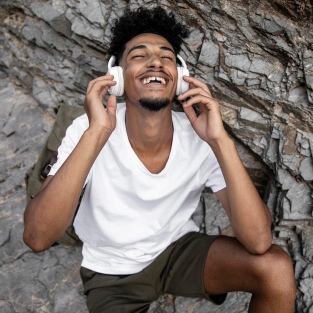 Homem feliz em tiro médio usando fones de ouvido Foto gratuita