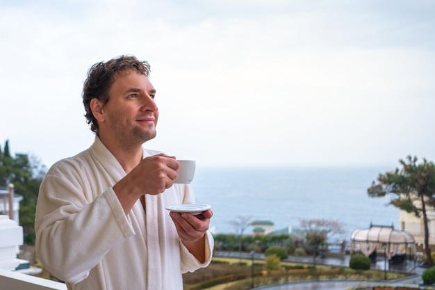 Homem feliz em um roupão branco encontra a manhã com uma xícara de chá ou café em um fundo do mar. o conceito de descanso, saúde e despertar. Foto Premium