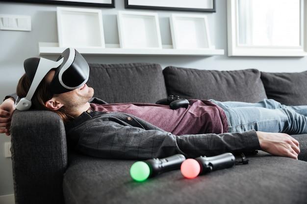 Homem feliz encontra-se no sofá em casa usando óculos 3d Foto gratuita
