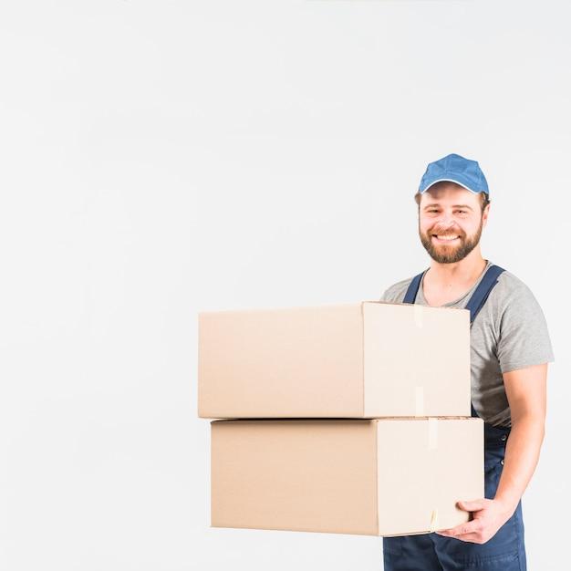 Homem feliz entrega permanente com grandes caixas Foto gratuita