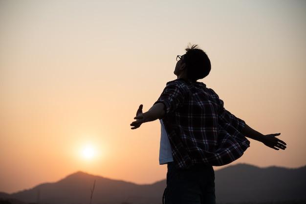 Homem feliz, espalhando os braços, estilo de vida de viagens, conceito de sucesso de liberdade. Foto Premium