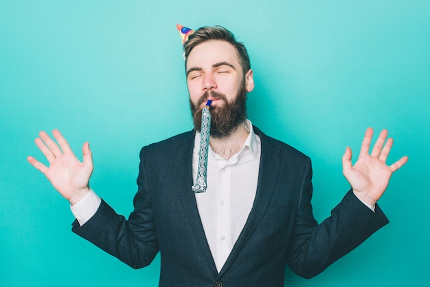 Homem feliz está de pé e aproveitando o momento usando um chapéu de festa Foto Premium