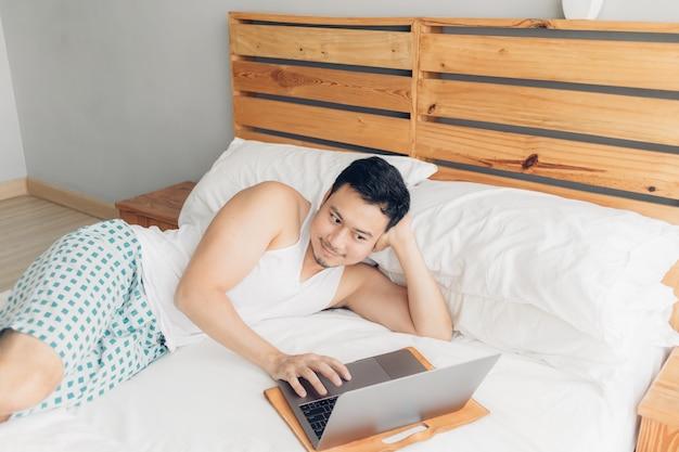 Homem feliz está trabalhando com seu laptop na cama dele. conceito de estilo de vida bem sucedido freelancer. Foto Premium