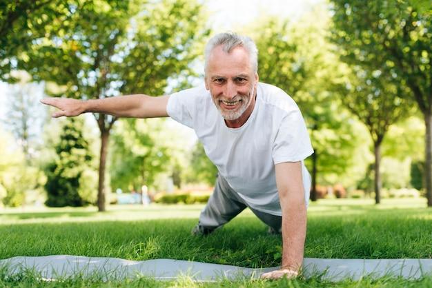 Homem feliz fazendo flexões na natureza Foto gratuita
