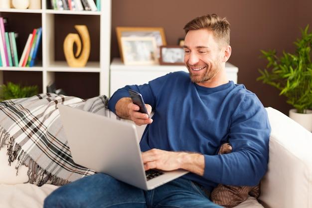 Homem feliz lendo o código qr pelo celular em casa Foto gratuita