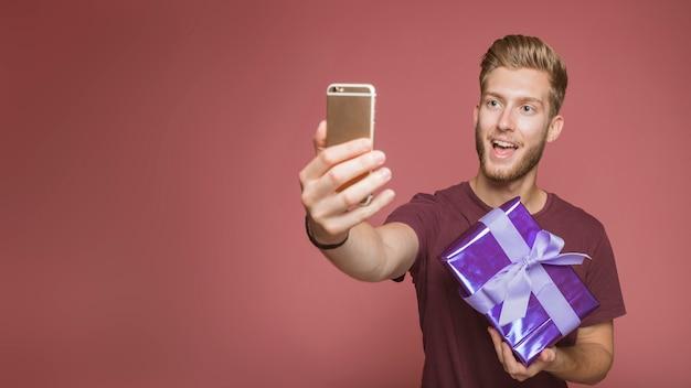 Homem feliz, levando, selfie, com, cellphone, segurando, caixa presente, contra, colorido, fundo Foto gratuita