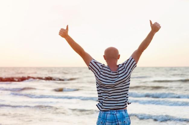 Homem feliz levanta os braços contra o mar Foto Premium