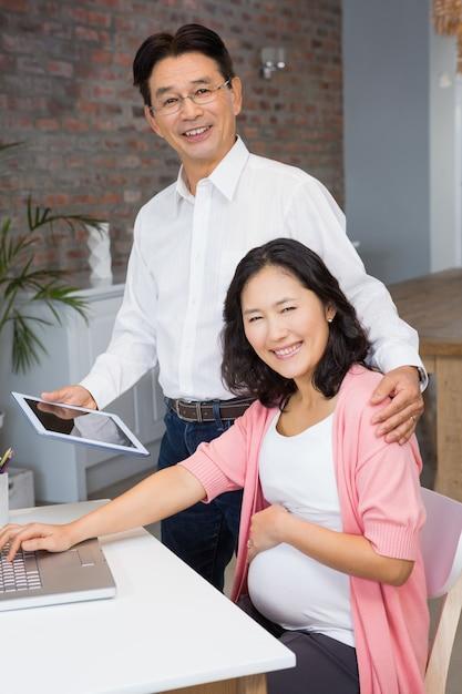 Homem feliz mostrando tablet para sua esposa grávida em casa Foto Premium