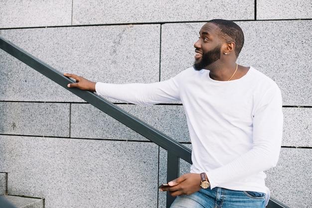 Homem feliz na escada olhando para cima Foto gratuita