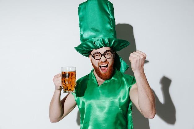 Homem feliz na fantasia de st.patriks segurando cerveja Foto gratuita