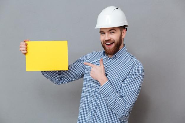Homem feliz no capacete segurando branches Foto gratuita