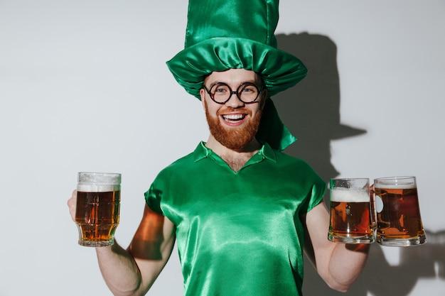 Homem feliz no traje de st.patriks segurando copos Foto gratuita