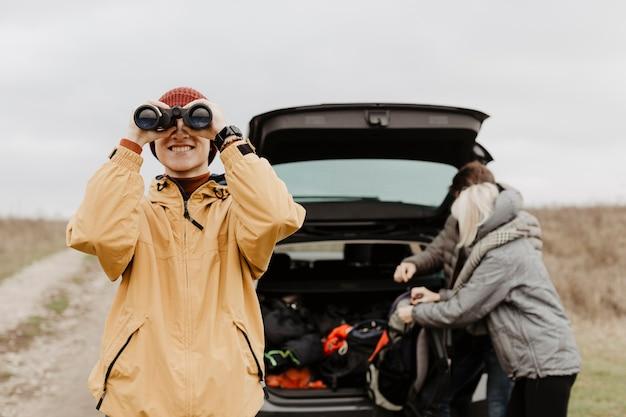 Homem feliz olhando através de binóculos Foto gratuita