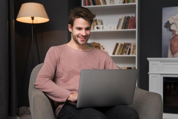 Homem feliz olhando para laptop Foto gratuita