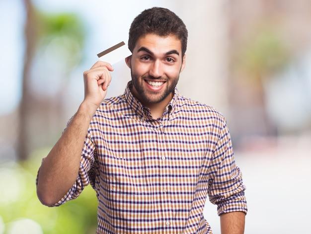 Homem feliz que prende o cartão de crédito. Foto gratuita