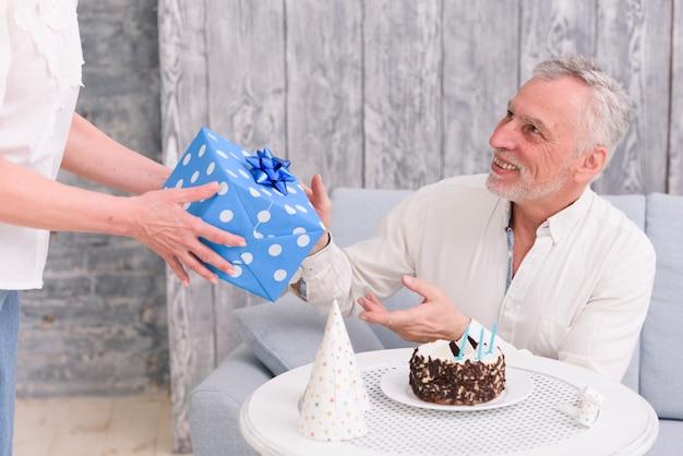 Homem feliz, recebendo, presente aniversário, de, seu, esposa, perto, bolo, e, chapéu partido, ligado, tabela Foto gratuita