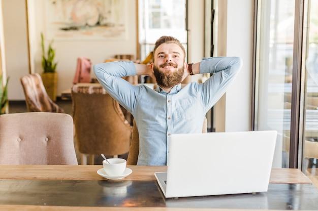 Homem feliz, relaxante, em, caf�, com, xícara café, e, laptop, escrivaninha Foto gratuita