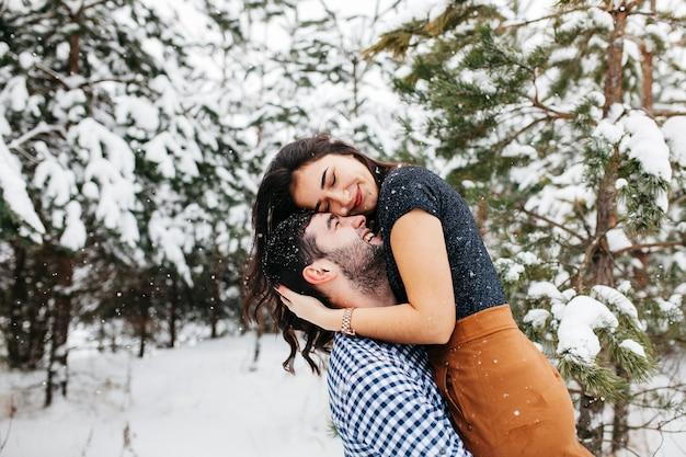 Homem feliz segurando a mulher nos braços na floresta de inverno Foto gratuita