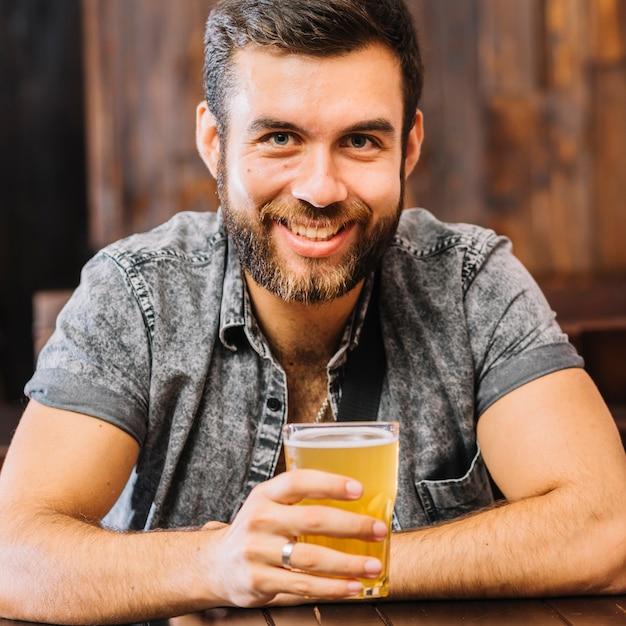 Homem feliz, segurando, copo cerveja Foto gratuita