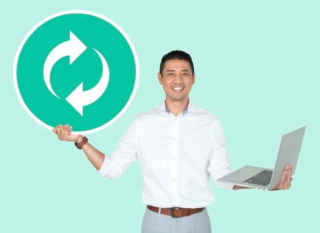 Homem feliz segurando um laptop e um ícone de atualização Foto gratuita