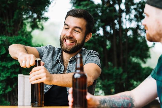 Homem feliz sentado com amigo abrindo a garrafa de cerveja ao ar livre Foto gratuita