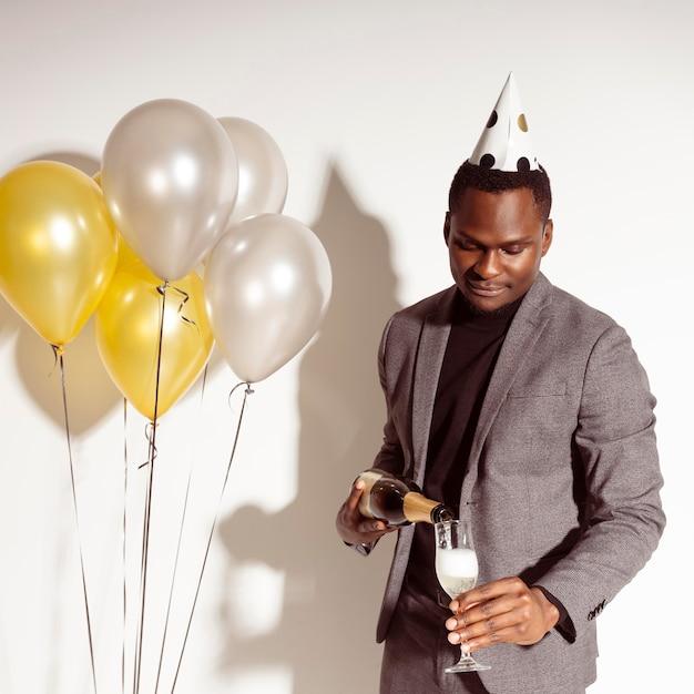 Homem feliz servindo champanhe na taça Foto gratuita