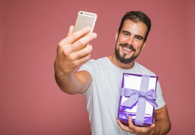 Homem feliz, tendo selfie com celular segurando a caixa de presente Foto gratuita
