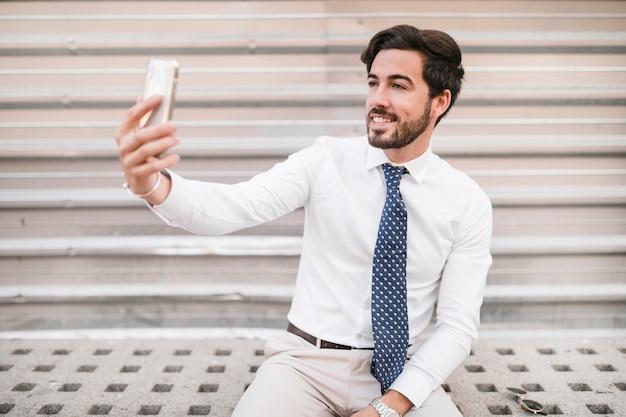 Homem feliz tomando selfie com smartphone Foto gratuita