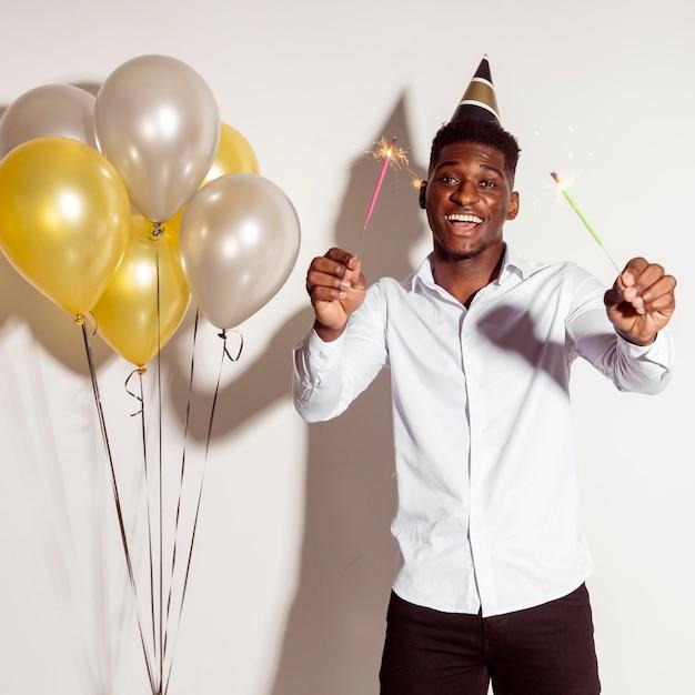 Homem feliz usando chapéu de festa e segurando estrelinhas Foto gratuita