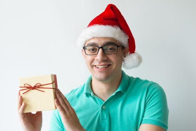 Homem feliz usando chapéu de papai noel e segurando a caixa de presente Foto gratuita