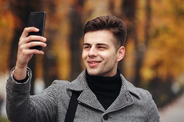 Homem feliz vestido calorosamente tirando foto da natureza ou fazendo selfie usando smartphone preto, enquanto caminhava no parque Foto gratuita