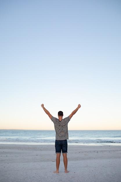 Homem, ficar, com, braços cima, praia Foto gratuita