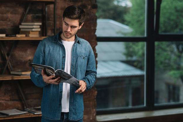 Homem, ficar, perto, a, prateleira leitura, revista Foto gratuita