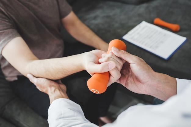 Homem fisioterapeuta dando exercício com tratamento com halteres sobre o braço e ombro apy conceito Foto Premium