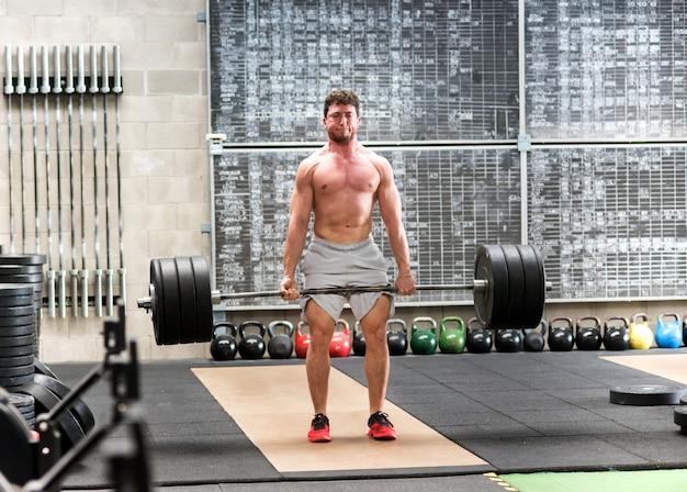 Homem forte deadlifter treinando com pesos pesados Foto Premium