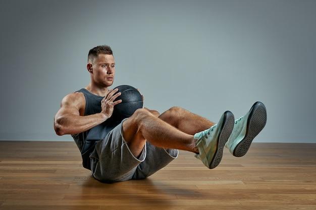 Homem forte fazendo exercício com bola med. foto do corpo perfeito do homem no fundo cinzento. força e motivação. Foto Premium