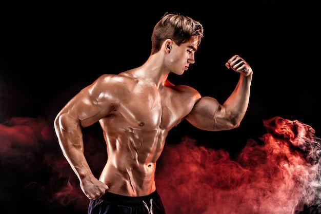 Homem forte fisiculturista com abs perfeito, ombros, bíceps, tríceps, peito, posando em fumaça levante a mão. Foto Premium