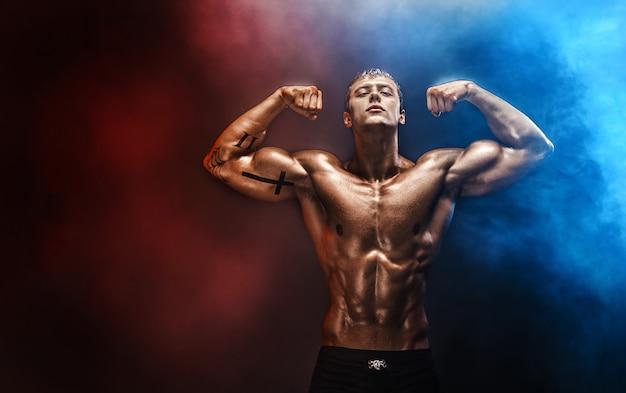 Homem forte fisiculturista com abs perfeito, ombros, bíceps, tríceps, peito. Foto Premium