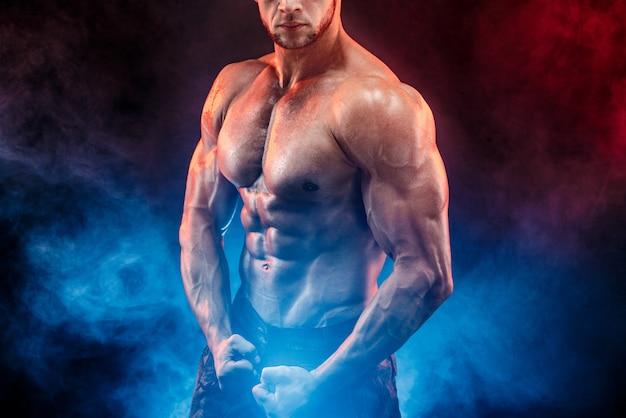 Homem forte fisiculturista em calças militares com abs perfeito, ombros, bíceps, tríceps, peito Foto Premium