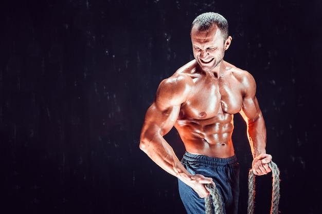 Homem forte sem camisa fisiculturista malhando duro com corda Foto Premium