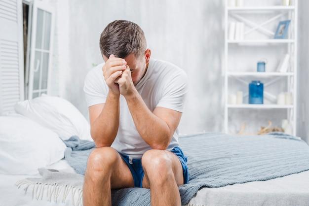 Homem frustrado com dor de cabeça, sentado na cama em casa Foto gratuita