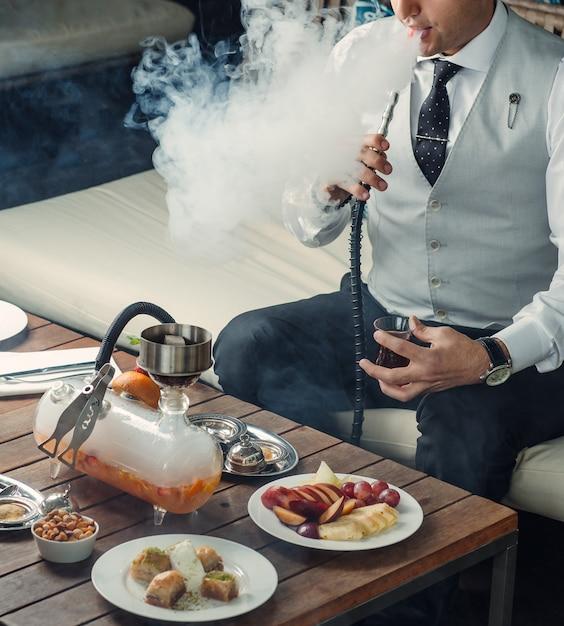 Homem fumando cachimbo de frutas de cachimbo no salão shisha Foto gratuita