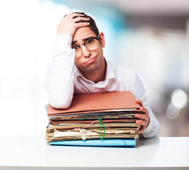 Homem furado olhando para uma pilha de papéis com uma mão na testa Foto gratuita