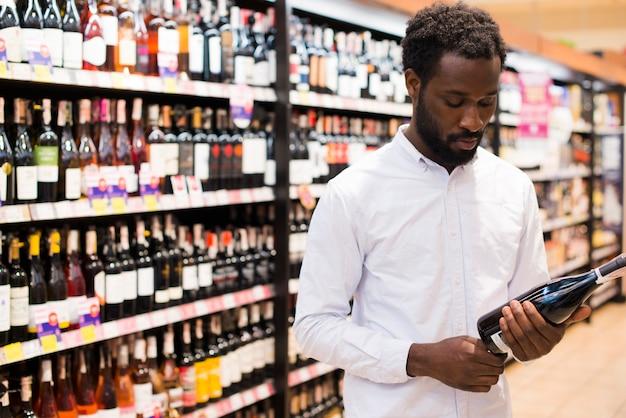 Homem, garrafa escolhendo, de, vinho, em, álcool, seção Foto gratuita