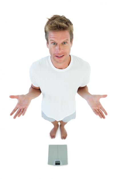 Homem gesticulando na frente de uma balança   Foto Premium