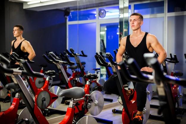 Homem girando em uma bicicleta em uma academia Foto gratuita