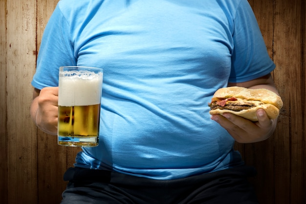 Homem gordo com cervejas e hambúrguer na mão Foto Premium