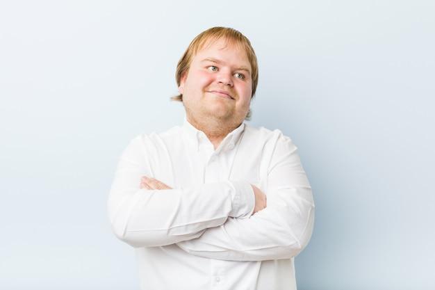 Homem gordo do ruivo autêntico novo que sorri seguro com braços cruzados. Foto Premium
