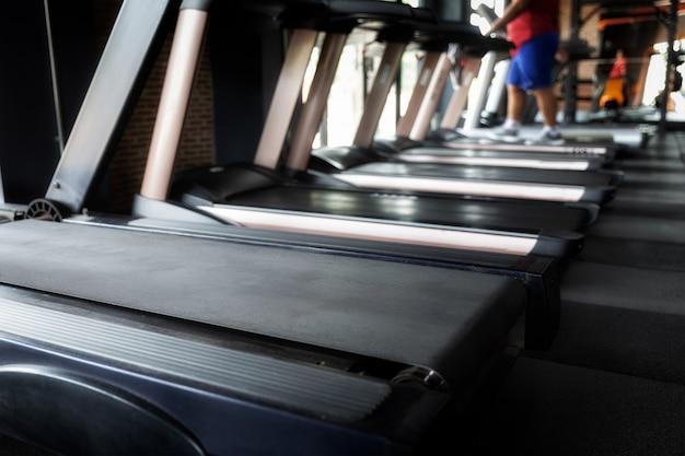 Homem gordo, exercitando-se na esteira em uma academia. focado na esteira. Foto Premium