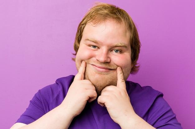 Homem gordo jovem ruiva autêntica duvidando entre duas opções. Foto Premium